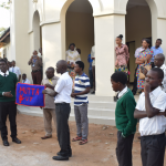 Deaf students handling the weaved carpet to their headmaster in his name at the main parade