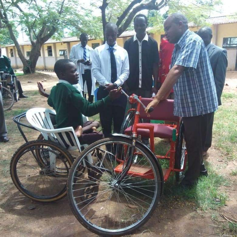Handing a three-foot bike to student Lucas Ndebile